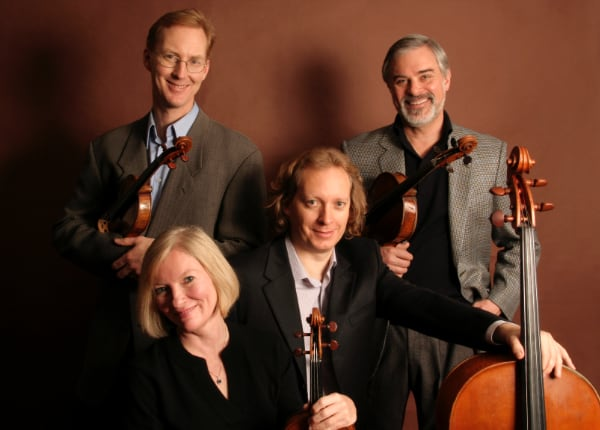 The four members of the American String Quartet pose with their instruments in front of a plain background