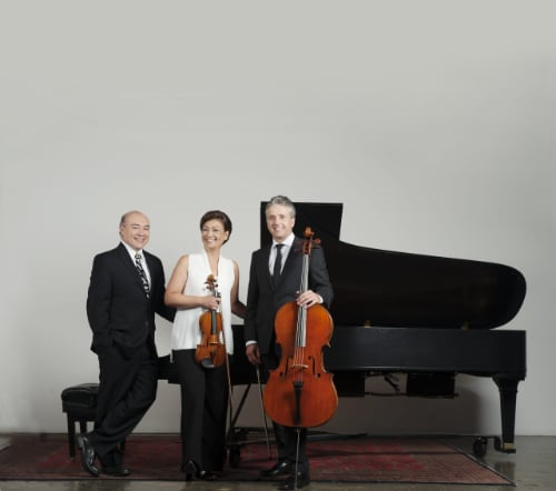 A distance shot of members of the Gryphon Trio pose at the piano with their instruments in front of a blank white wall