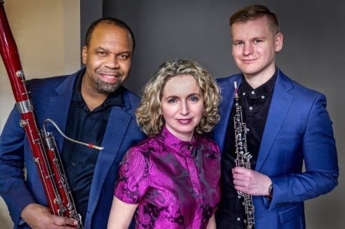 Members of the Poulenc Trio pose with their instruments in front of a plain background