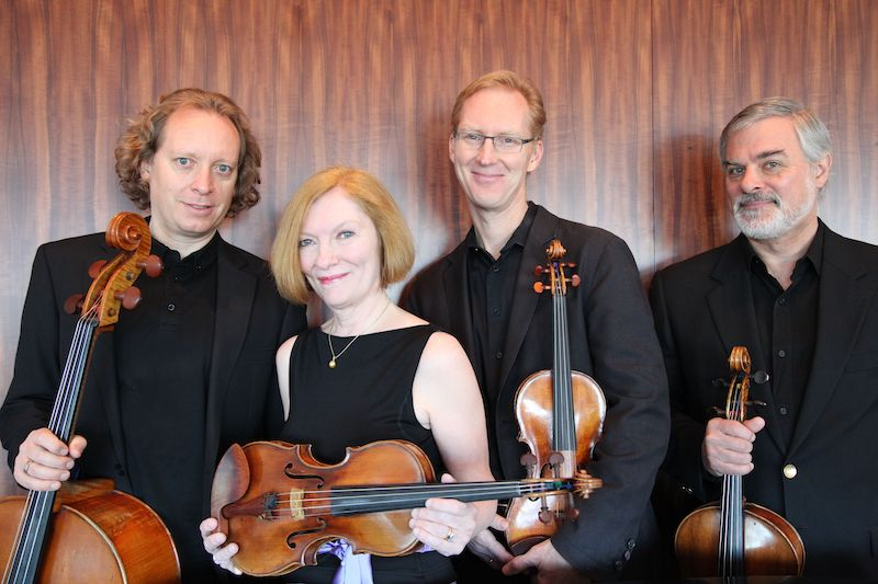 group photo of the american string quartet holding their instruments